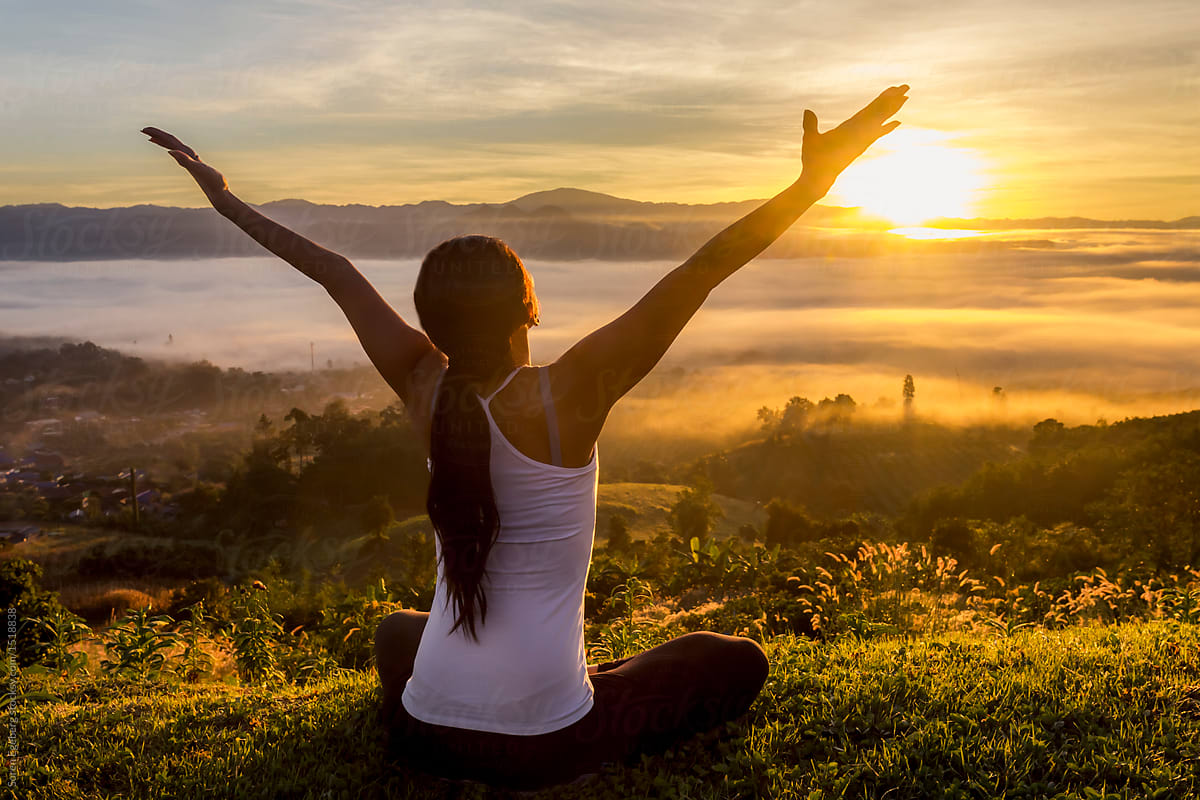 Peaceful woman meditating on a mountain at sunrise by Soren ...
