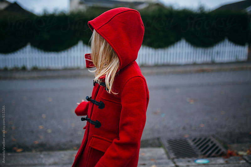 Side View Of A Little Girl in A Red Hooded Coat in front of a white Picket Fence by Amanda Voelker for Stocksy United
