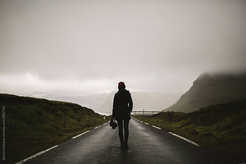 Woman Standing in the Middle of a Foggy Road by Daniel Inskeep for Stocksy United