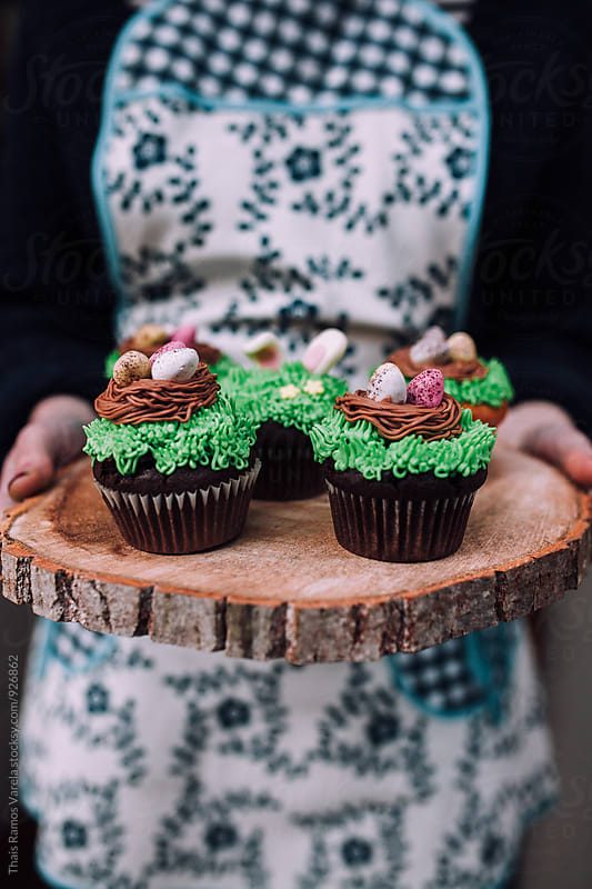 girl holding cupcakes above wood by Thais Ramos Varela for Stocksy United