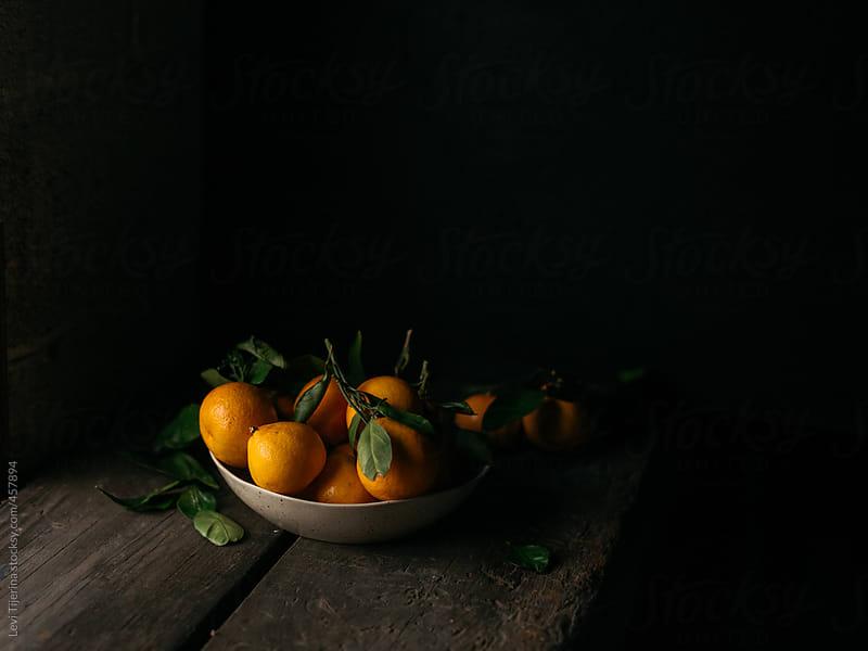 Tangerine in a bowl in a dark kitchen by Levi Tijerina for Stocksy United