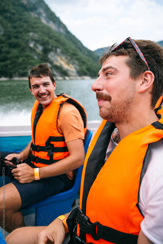 Friends having fun and laughing on a boat while their vacation by Alejandro Moreno de Carlos for Stocksy United