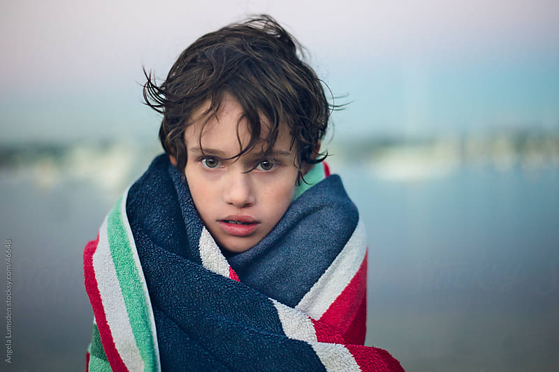 Boy wrapped in a towel after swimming at sunset by Angela Lumsden for Stocksy United
