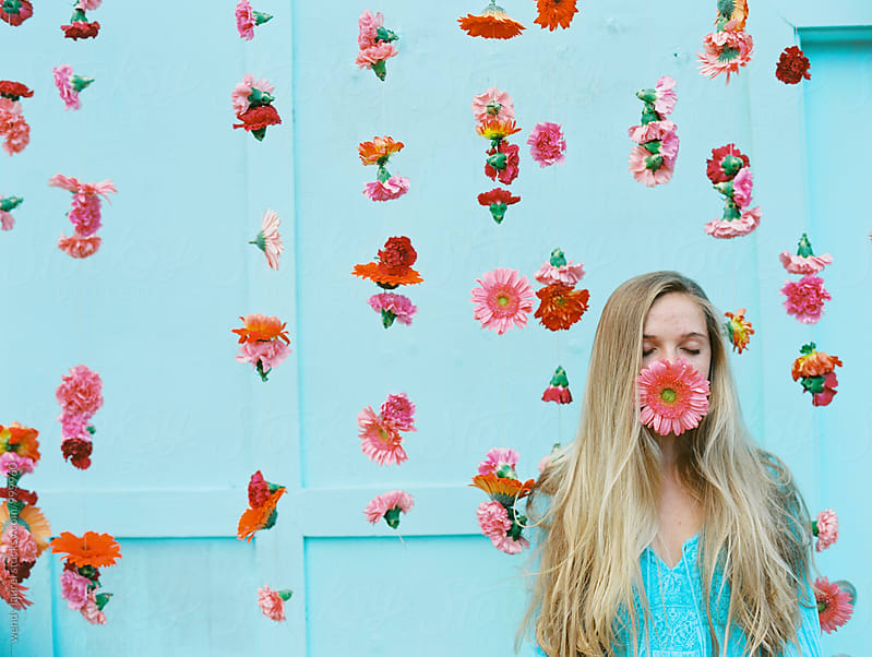 blonde teen girl with big pink flower in mouth in front of hanging pink flowers against blue wall by wendy laurel for Stocksy United