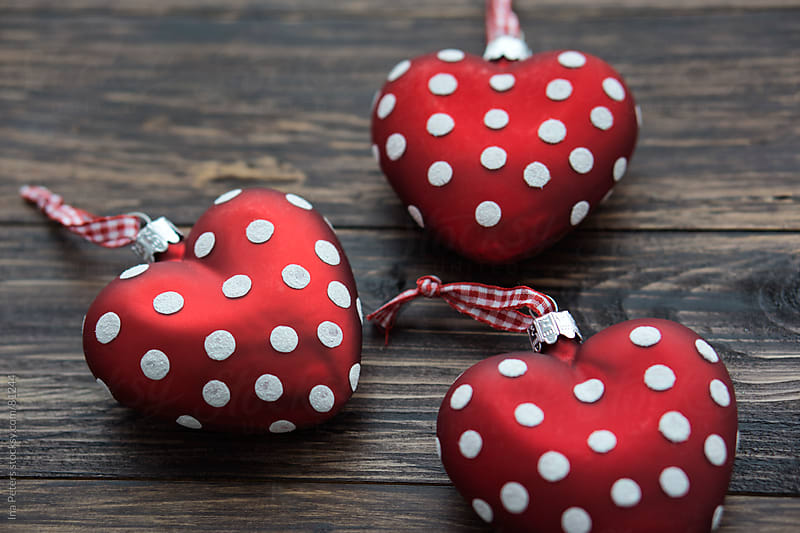 Christmas: Red Polka dots Christmas Ornaments on wooden table by Ina Peters for Stocksy United