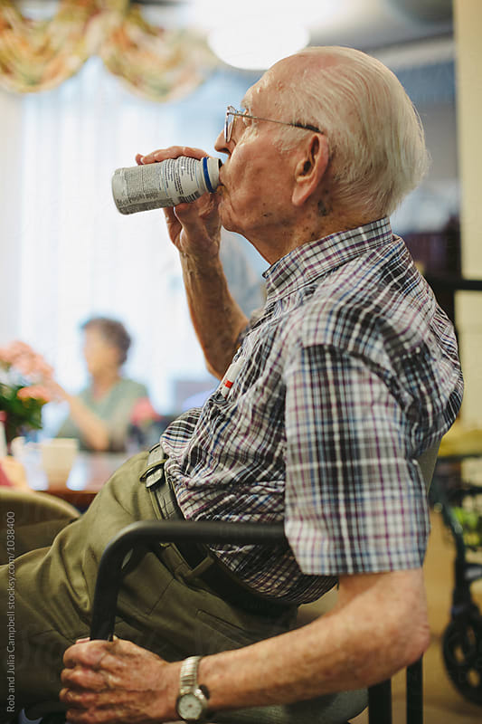 Senior caucasian man drinking nutritional drink inside by Rob and Julia Campbell for Stocksy United