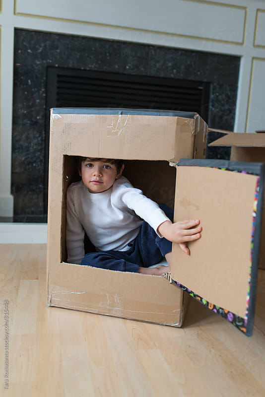 a young child inside a box, looking out a handmade flap by Tara Romasanta for Stocksy United
