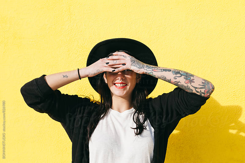 Alternative tattooed woman hiding her eyes standing in front of a yellow wall. by BONNINSTUDIO for Stocksy United