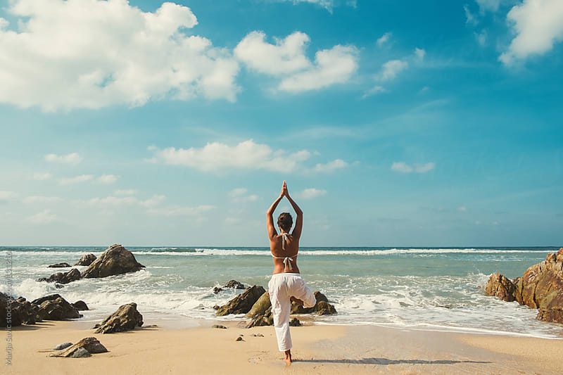 Woman doing yoga by the beach on a sunny day. by Marija Savic for Stocksy United