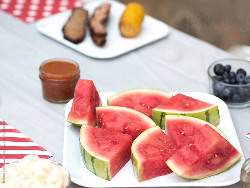 Watermelon on plate with other barbeque food by Jeremy Pawlowski for Stocksy United