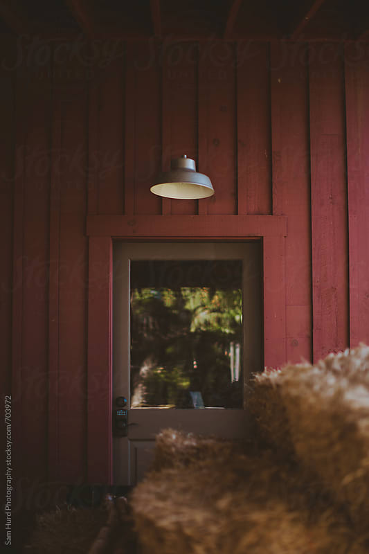 stack of hay in front of red barn by Sam Hurd Photography for Stocksy United