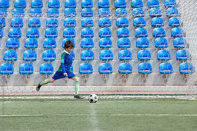 Young football player preparing for a corner kick in a game by Lawrence del Mundo for Stocksy United