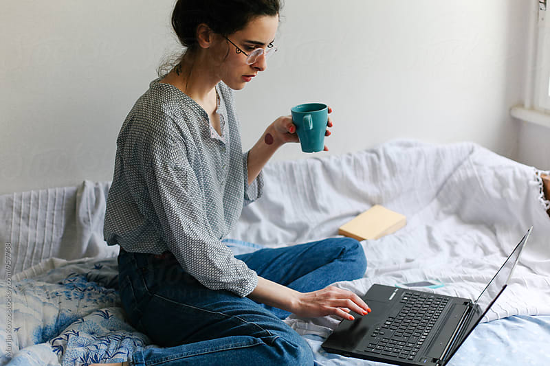 Woman drinking coffee on the bed, using her laptop by Marija Kovac for Stocksy United