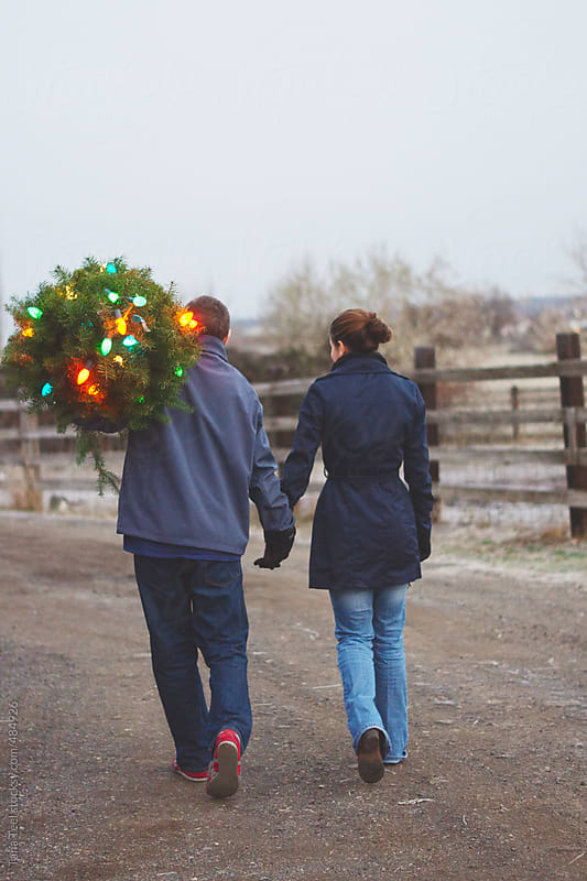 Couple walking with lighted Christmas tree by Tana Teel for Stocksy United