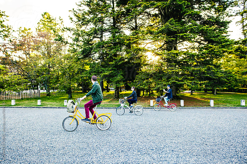 Tourist friends riding their bicycle in park at afternoon. by BONNINSTUDIO for Stocksy United