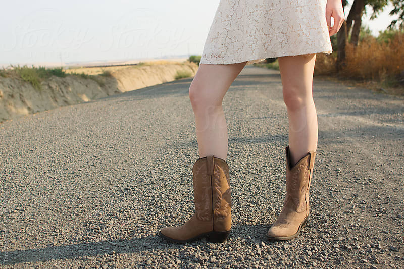 woman standing in middle of gravel road in cowboy boots and dress by Tana Teel for Stocksy United