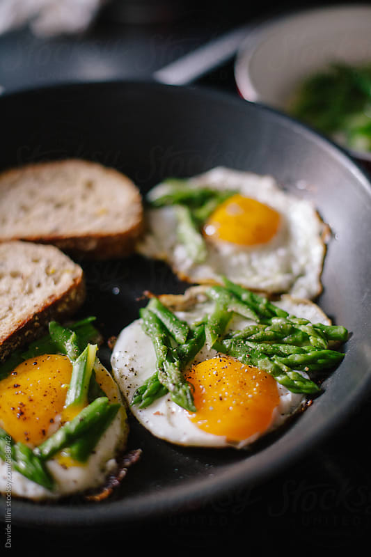 Fried eggs with asparagus by Davide Illini for Stocksy United