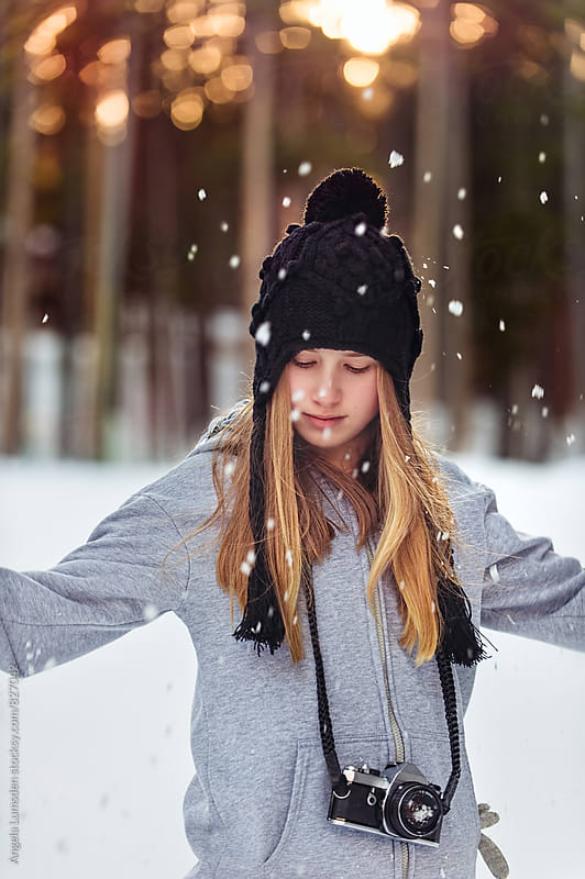 Teenage girl wearing a film camera throwing snow around outside in winter by Angela Lumsden for Stocksy United