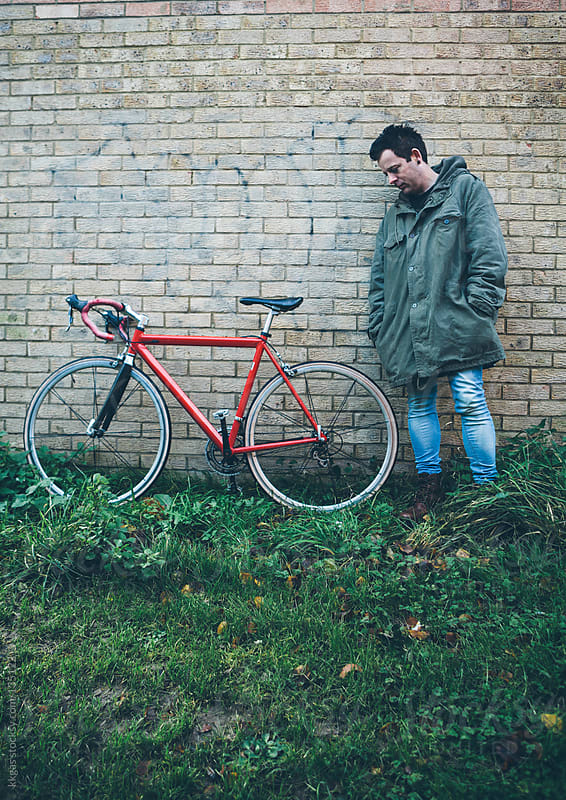 Man standing next to a bicycle. by kkgas for Stocksy United