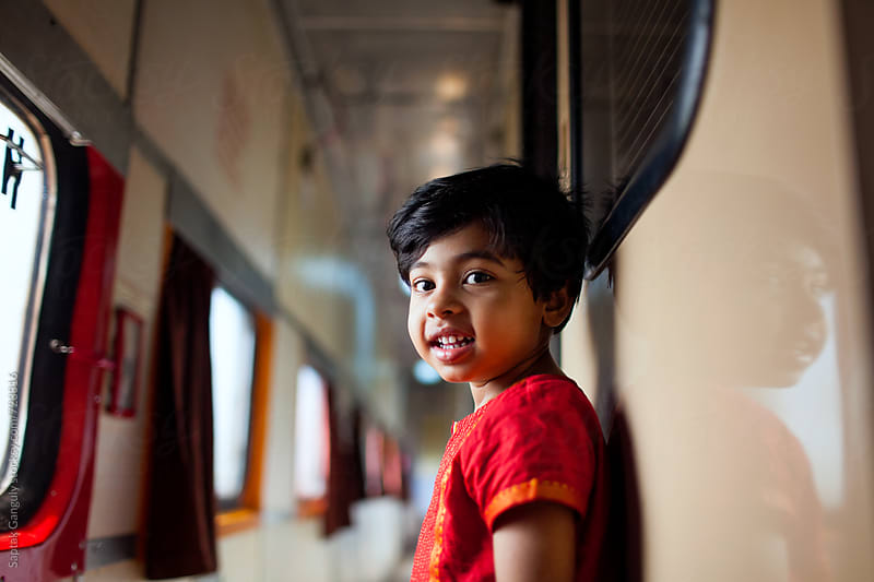 Little girl smiling at camera standing in a train corridor  by Saptak Ganguly for Stocksy United