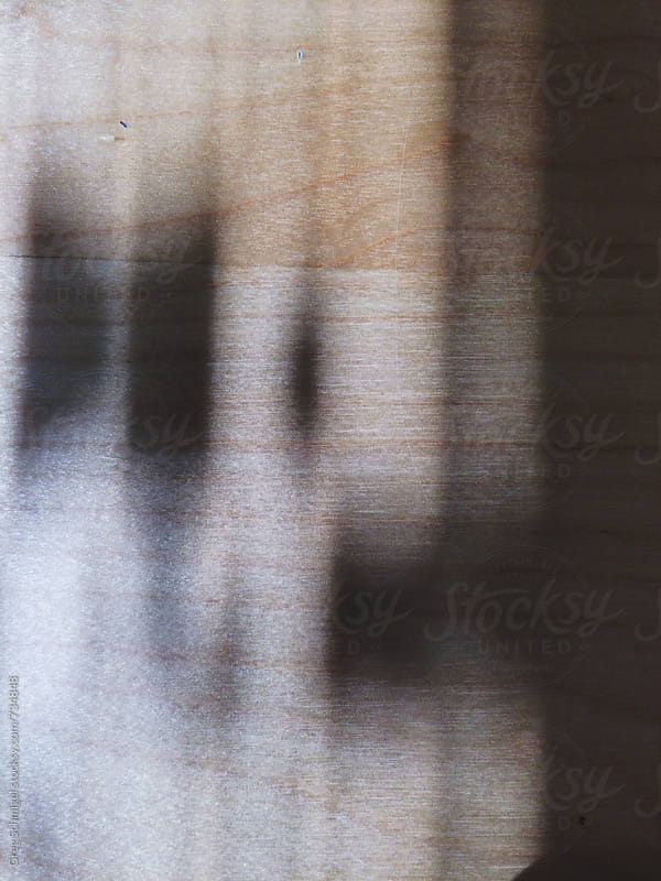 Detail of abstract shapes of natural light and shadow on a wooden surface, close up by Greg Schmigel for Stocksy United