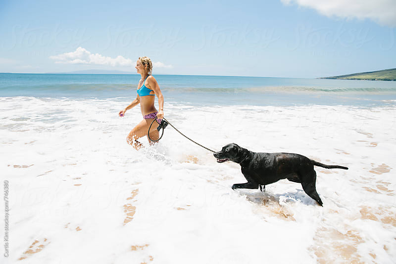 Blonde female waking dog at the beach on the shore by Curtis Kim for Stocksy United