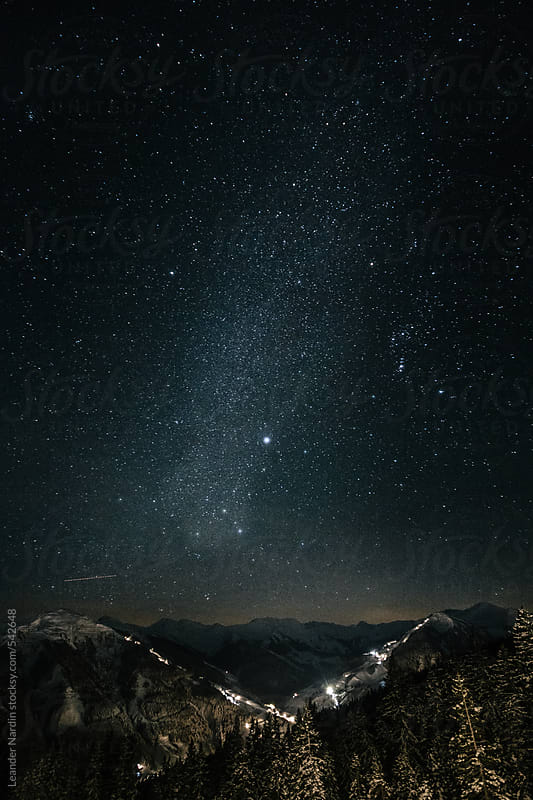 milky way above snowcovered austrian mountains by Leander Nardin for Stocksy United