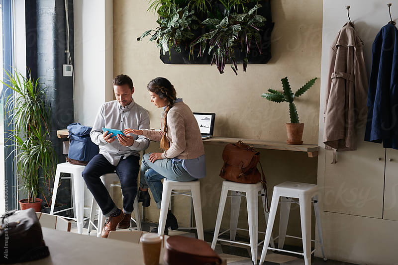Business partners looking at smart device in relaxed cafe atmosphere by Aila Images for Stocksy United