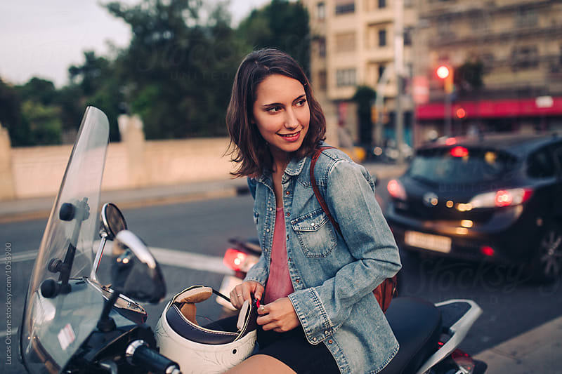 Young woman sitting on a motorbike by Lucas Ottone for Stocksy United
