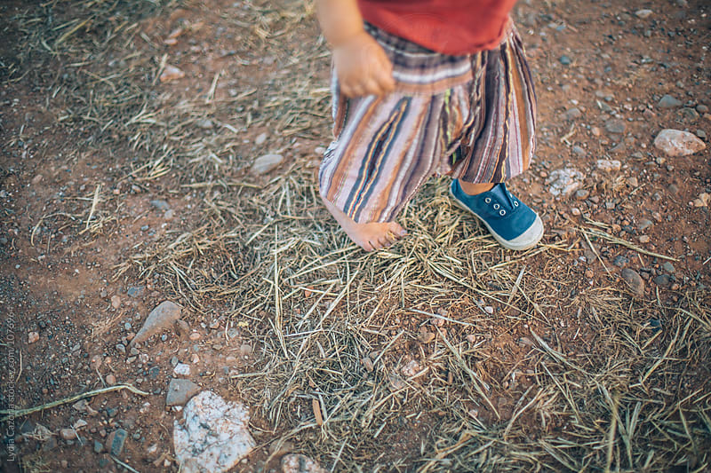 A child walking barefood  for the countryside by Lydia Cazorla for Stocksy United