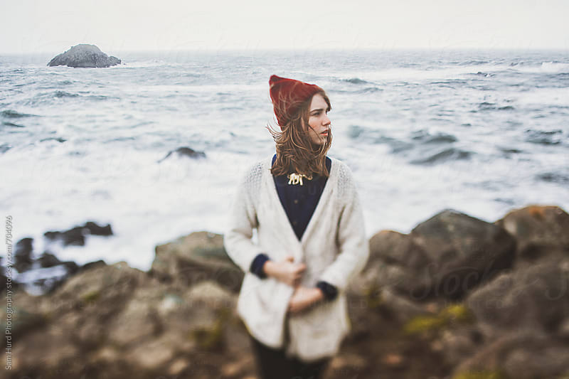 girl on a windy cliff in red beanie by Sam Hurd Photography for Stocksy United