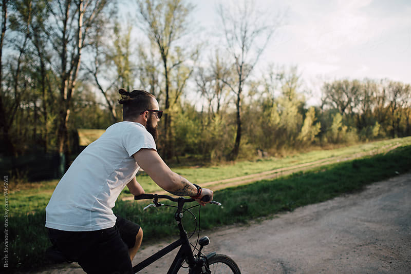 Man riding a bike in the forest by Boris Jovanovic for Stocksy United