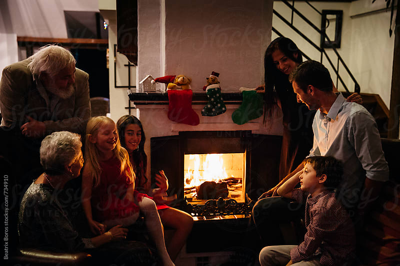 Gradparent,parents and kids all together at the fireplace at Christmas time by Beatrix Boros for Stocksy United