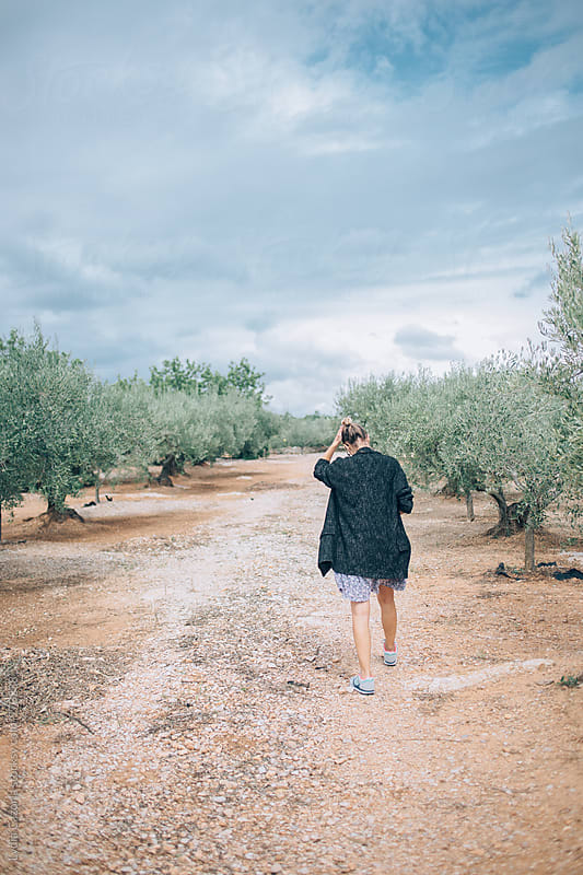 Young woman walking through olive groves by Lydia Cazorla for Stocksy United