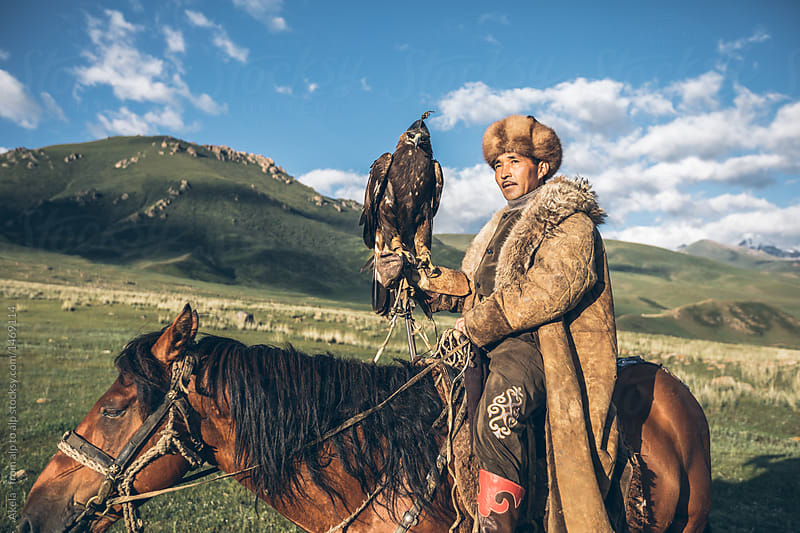 portrait of kyrgyz eagle hunter with a golden eagle sitting on his horse