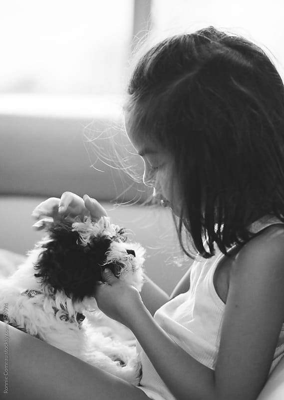 Girl Affectionately Petting Puppy by Ronnie Comeau for Stocksy United