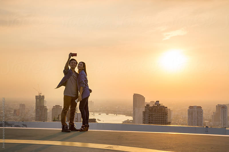 Young couple taking a selfie on a helicopter pad with the sun setting behind them  by Jovo Jovanovic for Stocksy United