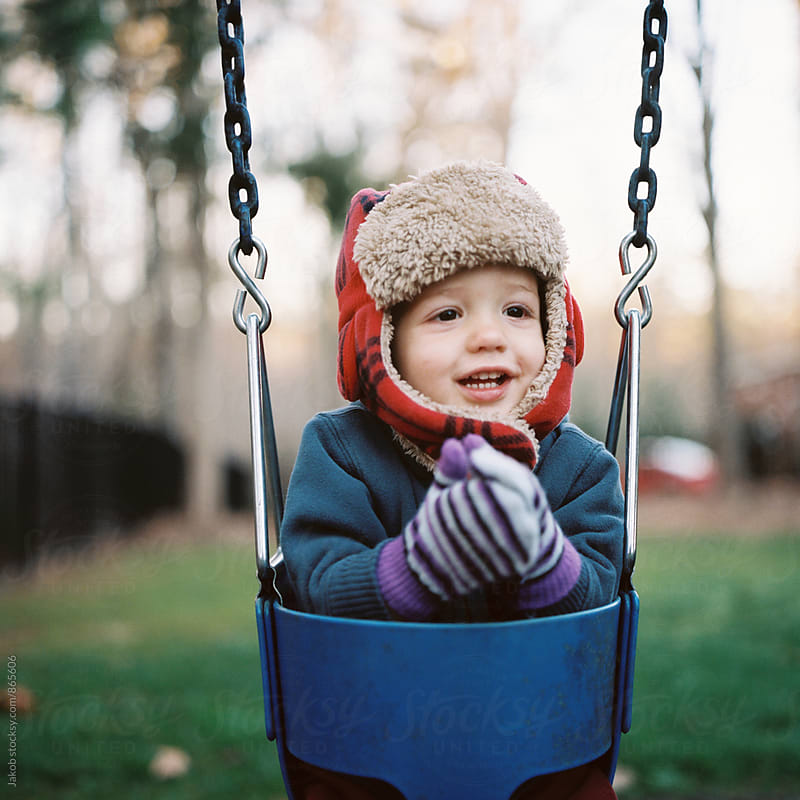Portrait of a young boy with a hat sitting in a swing by Jakob for Stocksy United