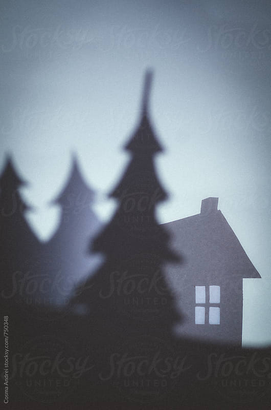Christmas greeting card with silhouette of pine tree and house at nigh with snow by Cosma Andrei for Stocksy United