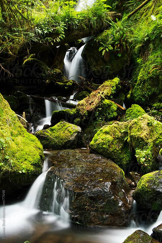 Waterfall flows through rocks by Thomas Shull for Stocksy United