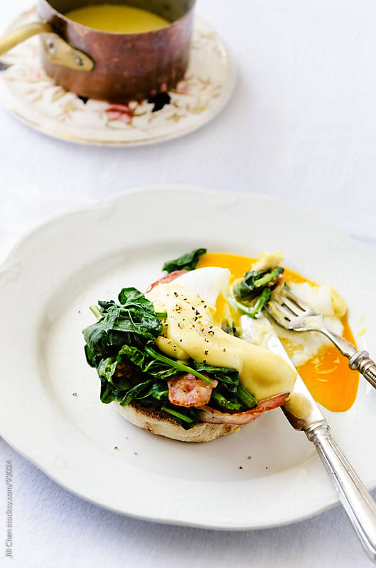 Eggs benedict with hollandaise sauce, spinach and bacon by Jill Chen for Stocksy United