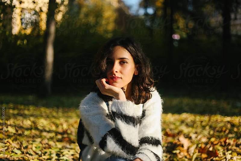 Beautiful woman sitting in a park, looking at the camera by Marija Kovac for Stocksy United