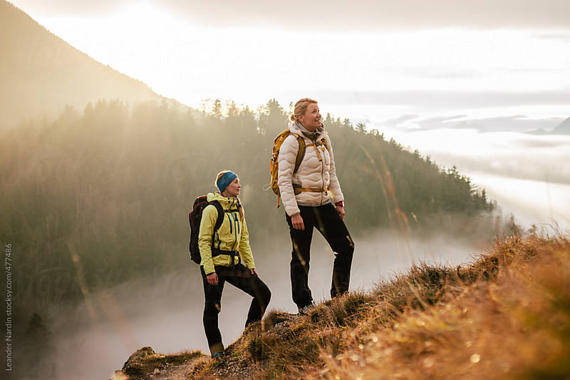 two female hiker on a mountain in autumnal scenery by Leander Nardin for Stocksy United