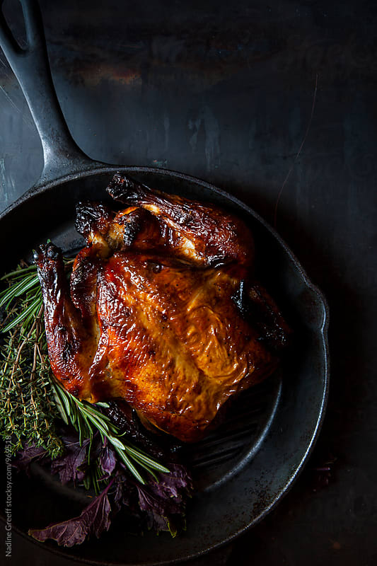 Roast chicken in cast iron skillet with herbs by Nadine Greeff for Stocksy United