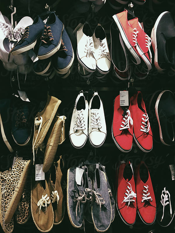 Shoes lined up on a wall in a store by Justin March for Stocksy United