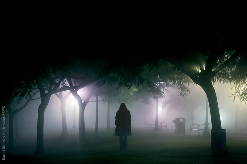 A silhouette emerges from foggy light in a park at night by Rachel Bellinsky for Stocksy United