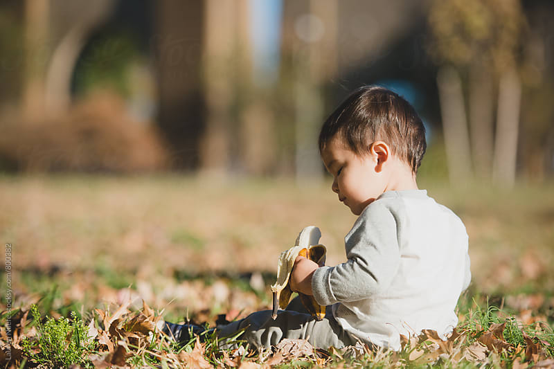 Little kid having a snack outside by Lauren Naefe for Stocksy United