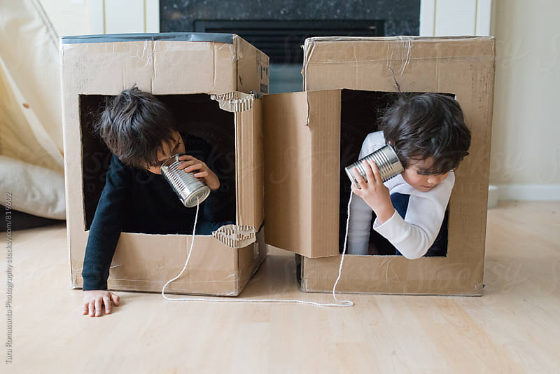 two children in boxes talking with a tin can telephone by Tara Romasanta for Stocksy United