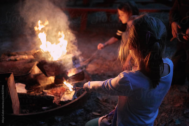 Two girls playing with campfire by Alicja Colon for Stocksy United