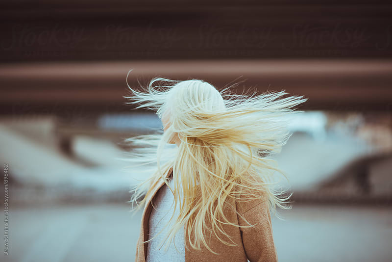 Young woman lets her hair flow in the wind  by Drew Schrimsher for Stocksy United